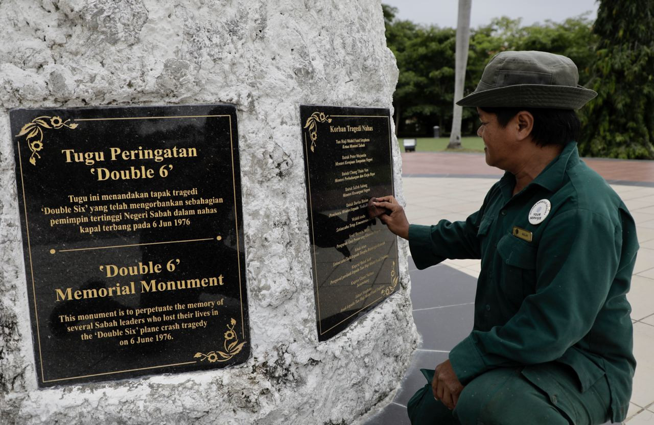 State landscape department gardener Azlan Karim wiping the nameplate of victims of the tragedy in September last year. – The Vibes file pic